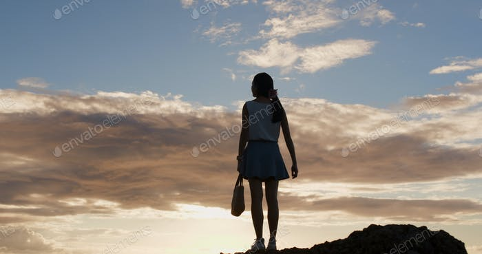 Silhouette of woman standing up to the mountain