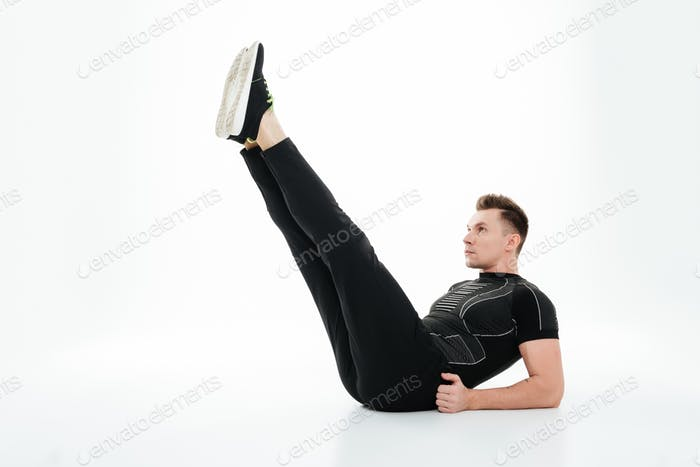 Young concentrated sportsman doing abdominal exercises on the floor