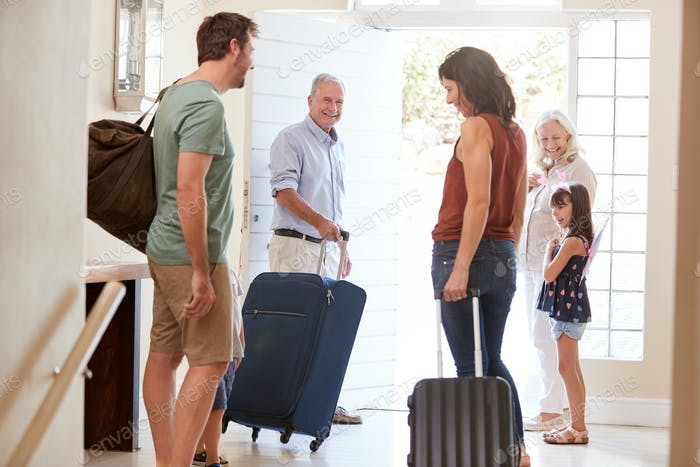 Three generation white family preparing to leave home to go on holiday, full length, close up
