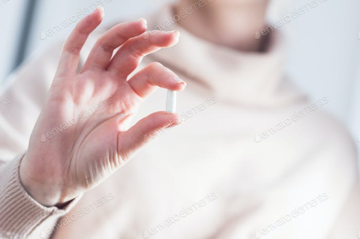 Woman holding a pill. Treatment, drug