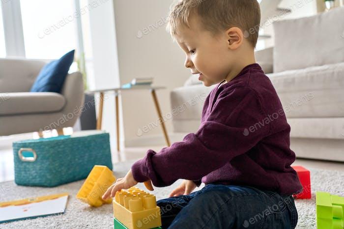 Lindo niño preescolar niño niño jugando sentado en el suelo en casa.