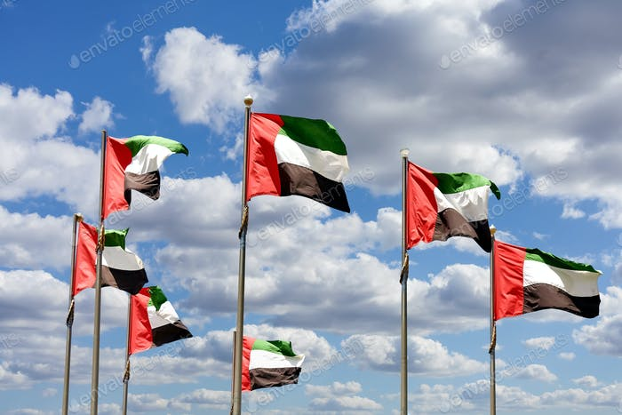 Seven United Arab Emirates flags against blue sky with clouds.