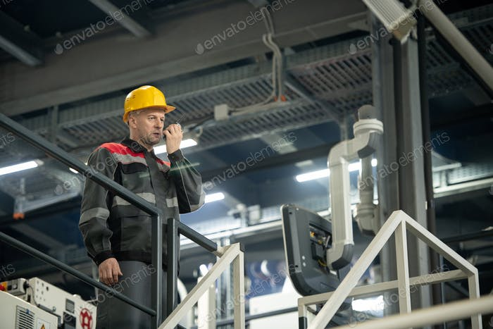 Confident mature foreman with hardhat on head and walkie talkie by his mouth