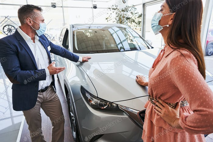 Sales specialist demonstrating the car to his interested customer