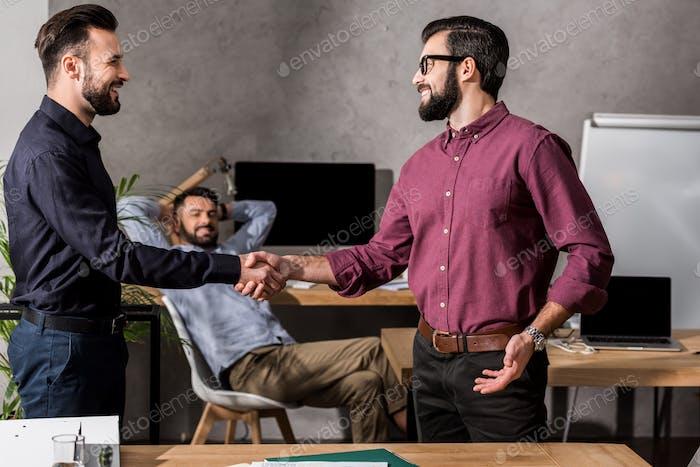 smiling businessmen shaking hands in office