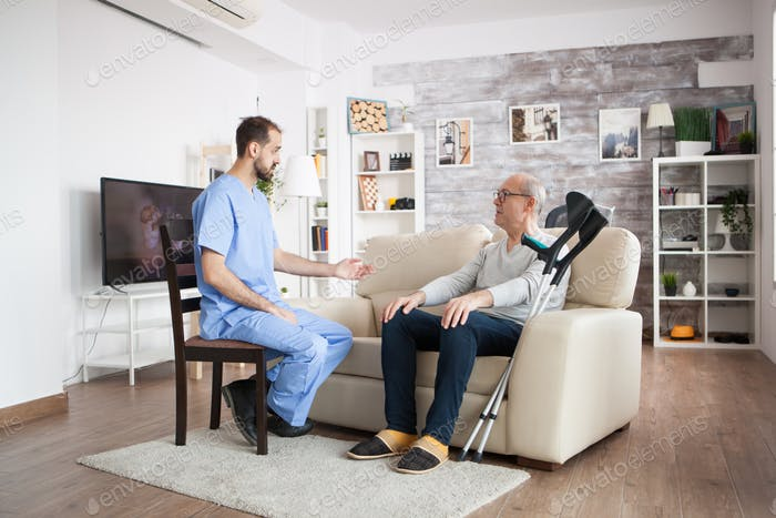 Male nurse on a chair in a nursing home talking with elderly age man