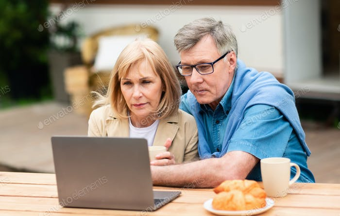 Serious mature couple using laptop computer near camper van outside
