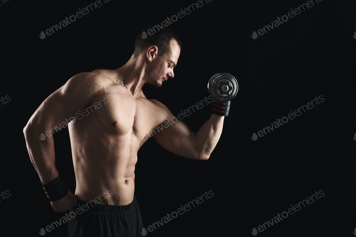 Strong athletic man with dumbbell showes naked muscular body