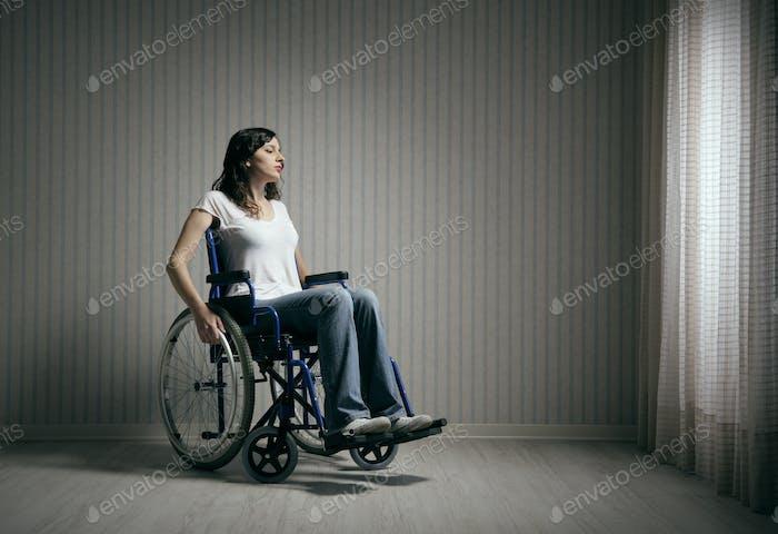 Sad woman sitting on wheelchair