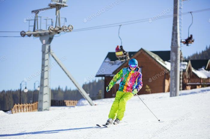 Junger Mann Skifahren bergab auf Winterort