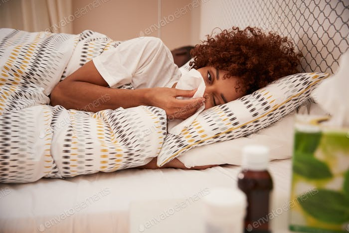 Millennial African American woman lying in bed blowing her nose into a tissue, side view, close up