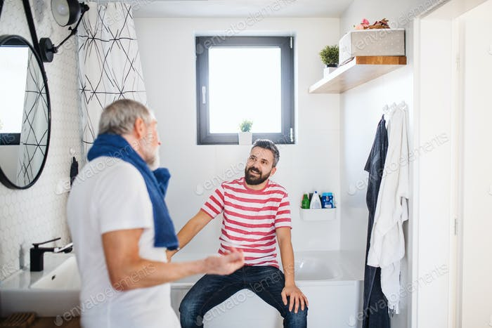 An adult hipster son and senior father in bathroom indoors at home, talking