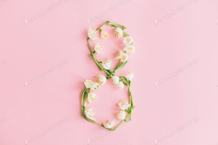 Floral number 8 made of spring flowers on pink background