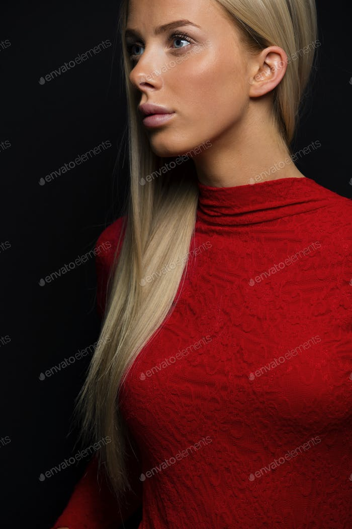 Dark portrait of a pretty blonde woman in red dress on black bakground