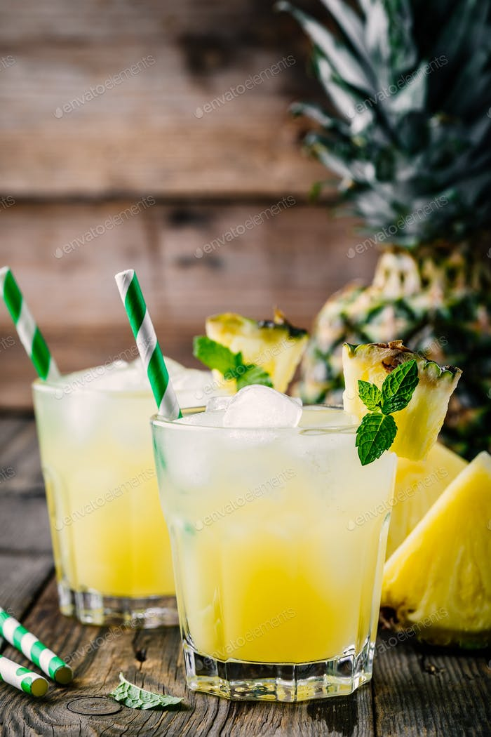 Fresh pineapple juice in two glasses with ice and mint on dark rustic background