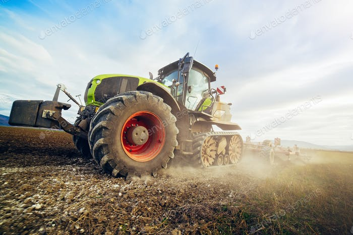Modern tractor working on the field. Tractor plowing fields preparing land for sowing