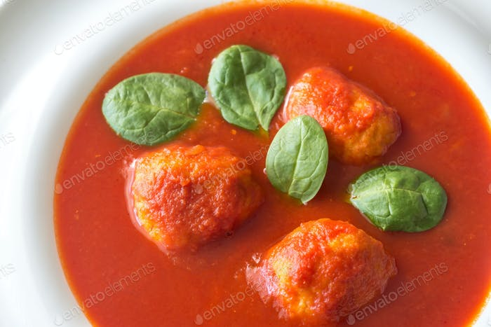 Portion of tomato soup with meatballs