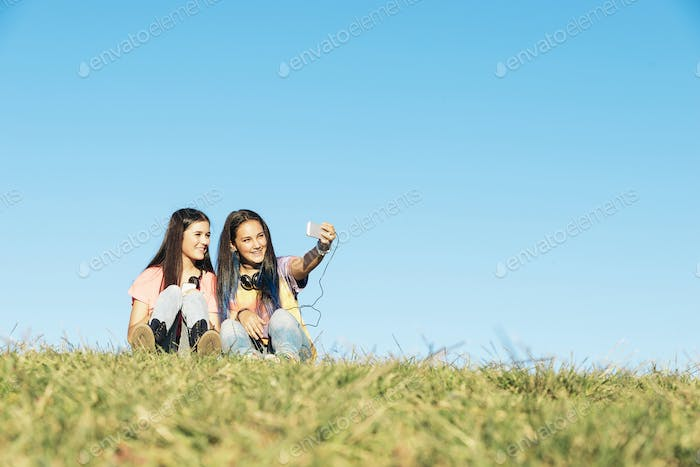 Two Teenage Girls Taking Selfie In Park