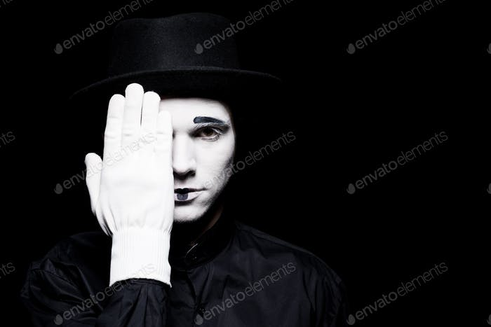 mime covering eye and looking at camera isolated on black