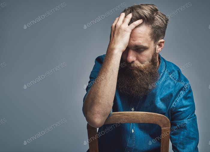 Depressed man with hand on forehead over gray