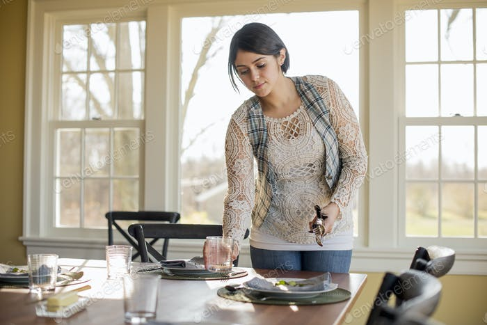 A woman setting the table for a meal.