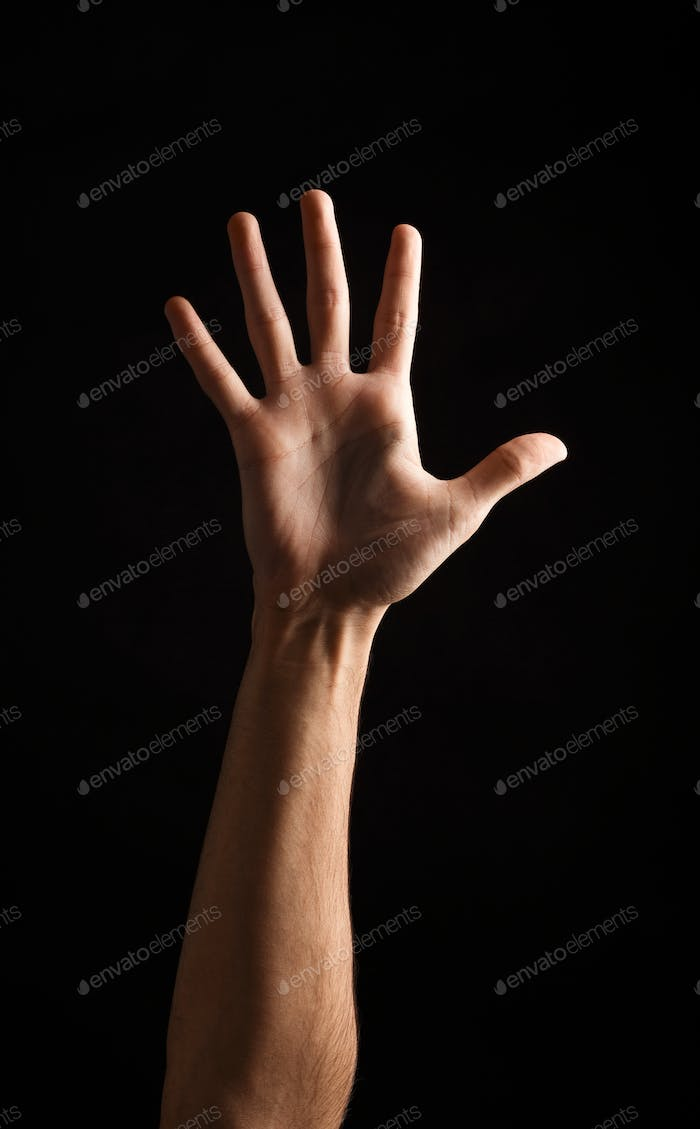 Male hand shows number five isolated at black