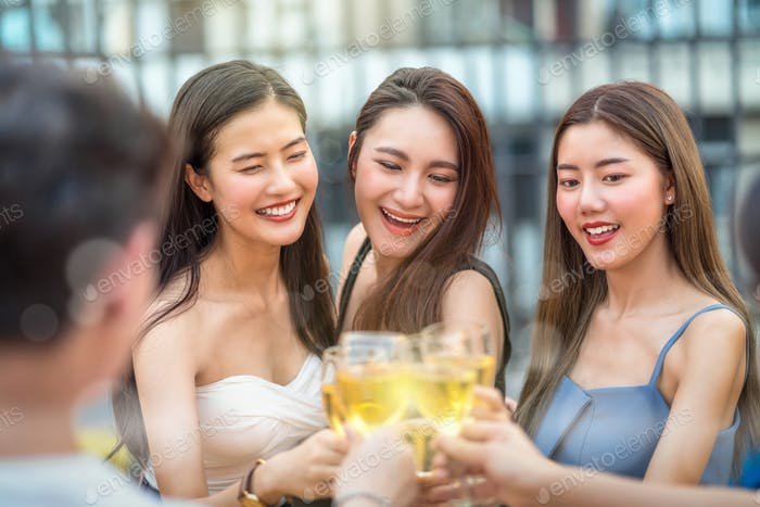 Happiness Asian Girl Friend Group celebrating and Cheering together with glass of wine at sunset