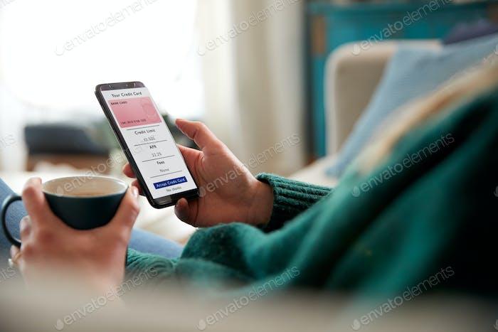 Nahaufnahme der Frau Bewerbung für Kreditkarte Online mit Handy zu Hause