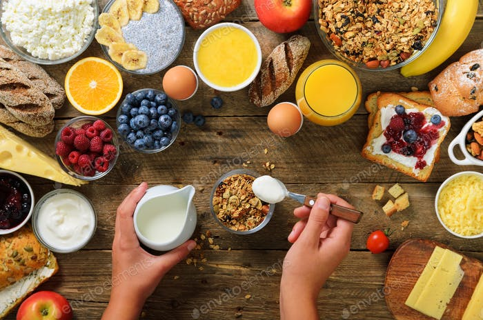 Girl cooking breakfast - granola with yogurt, fruits, berries, milk, yogurt, juice, cheese. Top view
