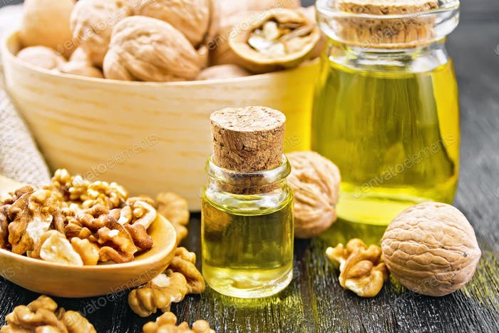 Oil walnut in two jars with spoon on board