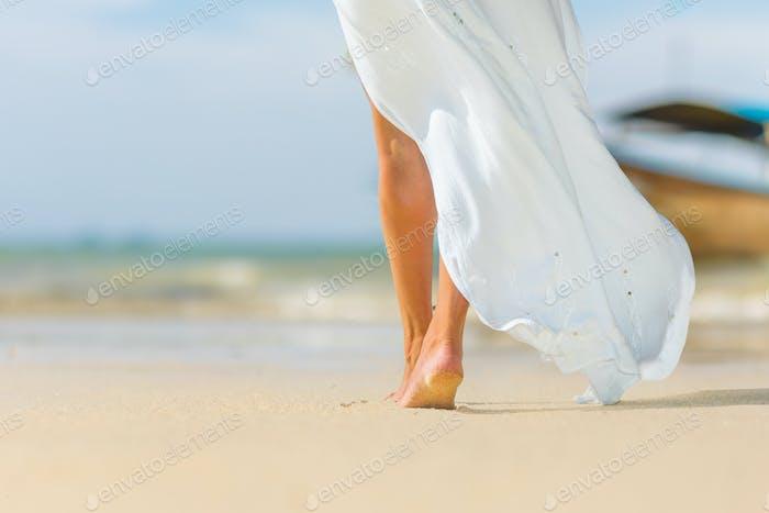 White pareo woman legs walking on tropical beach