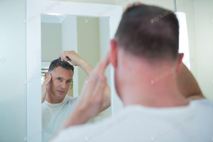 Mann kämmt seine Haare im Bad