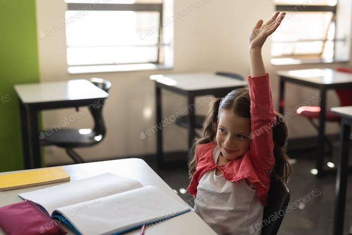 Side view of a smiling schoolgirl raising hand in classroom while sitting at desk