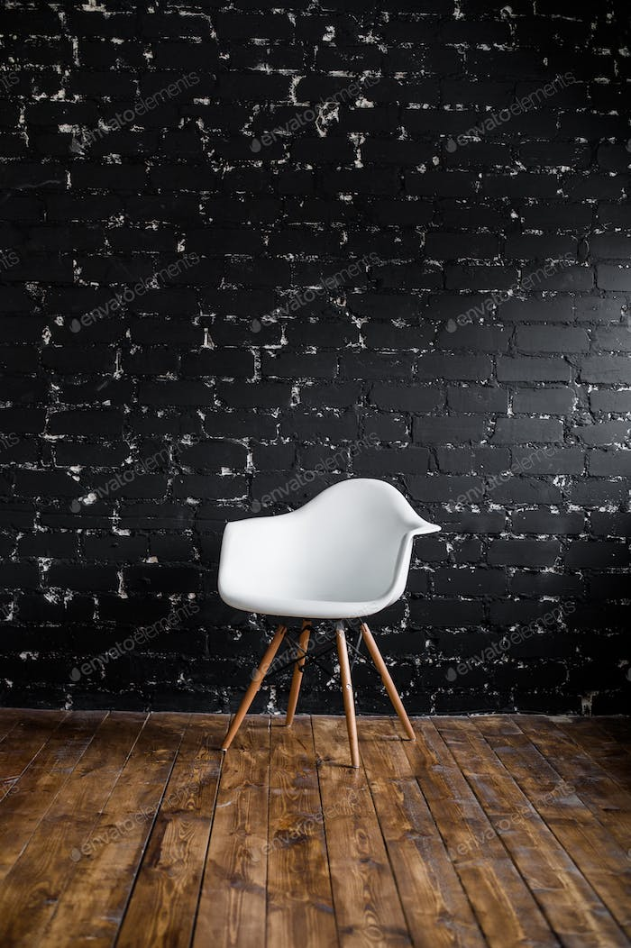 White chair standing in room on brown wooden floor over black brick wall