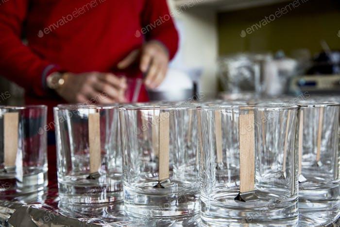 Nahaufnahme von leeren Gläsern mit Holzdochten, zur Kerzenherstellung.