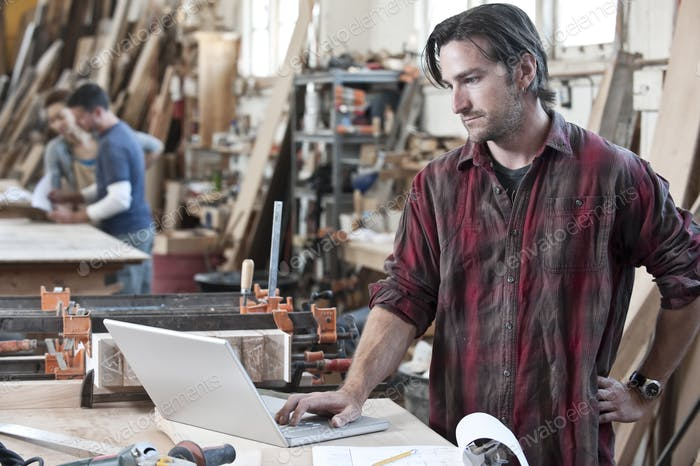 Caucasian man factory worker working on a lap top computer at a work station in a woodworking