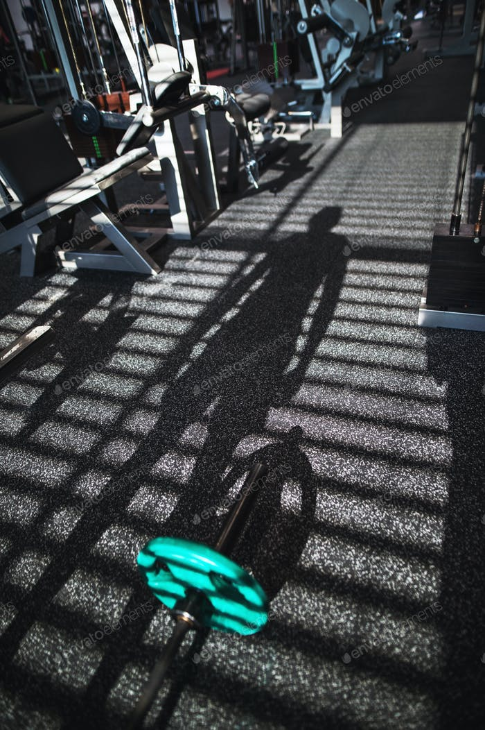 Gym with various exercise machines in it, a shadow of a person working out.