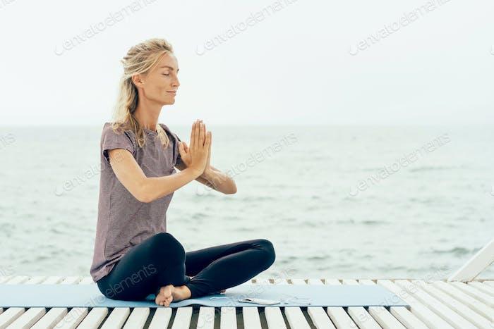 Junge Frau in Namaste Gruß Pose am Meer. Kopieren Sie den Leerraum für Text.