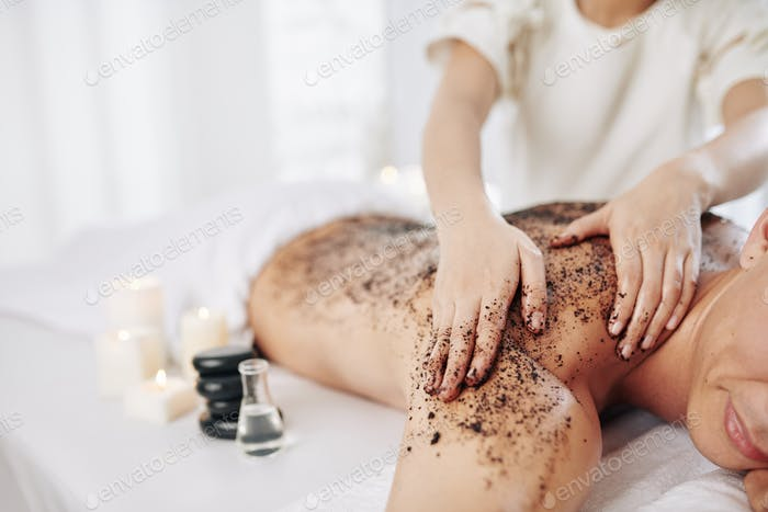 Massaging back with coffee scrub
