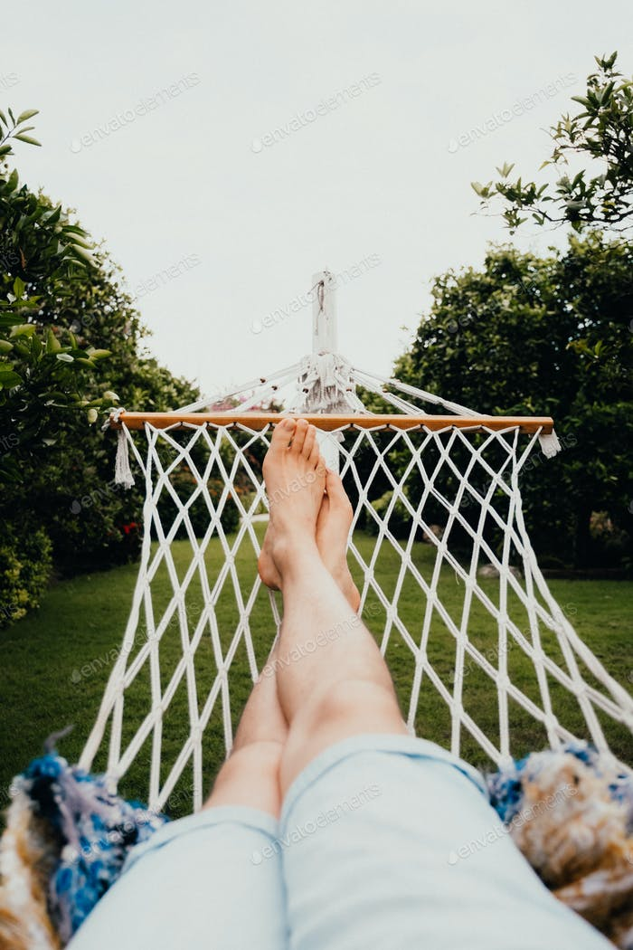 A man has a rest lying on a hammock at tropical garden. Travel and vacation concept