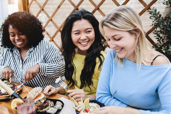 Young multiracial people having breakfast outdoor at patio restaurant - Focus on asian girl face