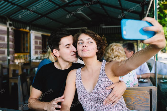 guy and the girl make selfie in the cafe outside