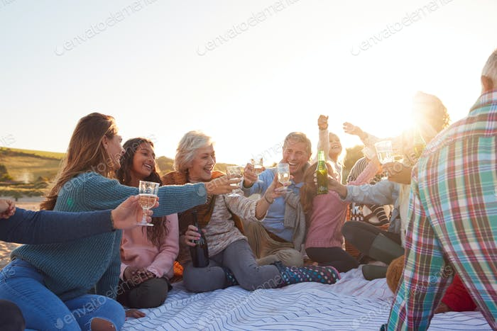 Multi-Generation Family Making A Toast With Alcohol On Winter Beach Vacation
