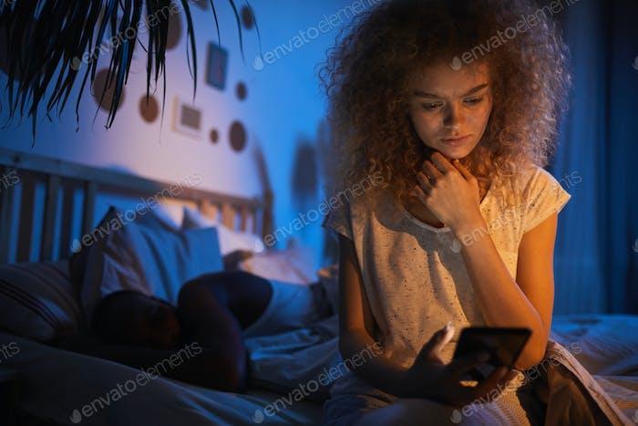 Junge Frau beim Lesen von Textnachrichten in der Nacht