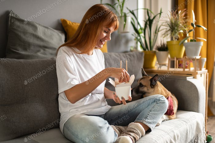 Cheerful woman eating Chinese food near dog