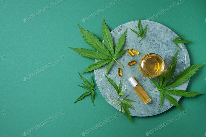 CBD oil, hemp oil capsules and cannabis leaves on green background. Flat lay, copy space. Cosmetics