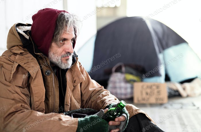 A homeless beggar man sitting outdoors, holding bottle of alcohol. Copy space.