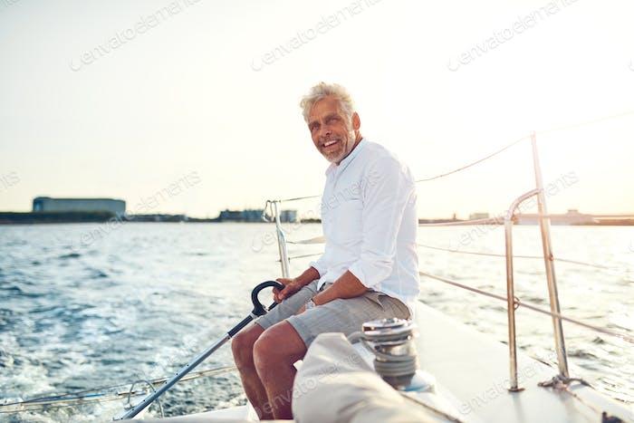 Smiling mature man sailing his boat along the coast