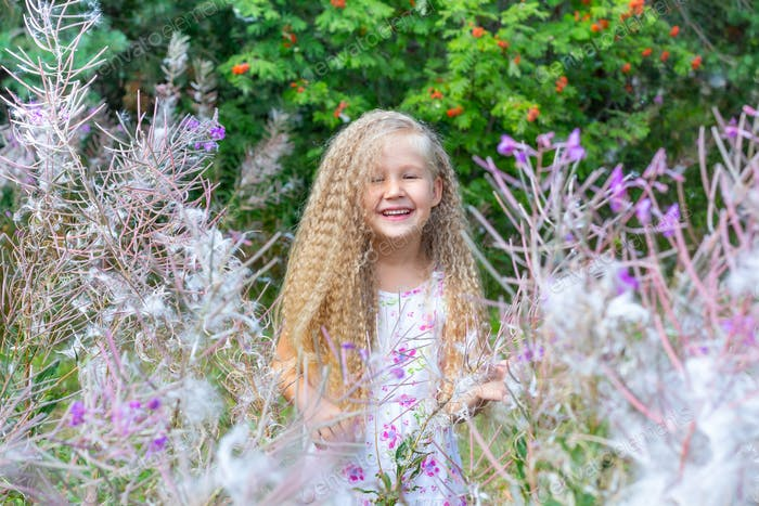 A little girl with curly long hair in a white sundress stands surrounded by blooming fireweed.