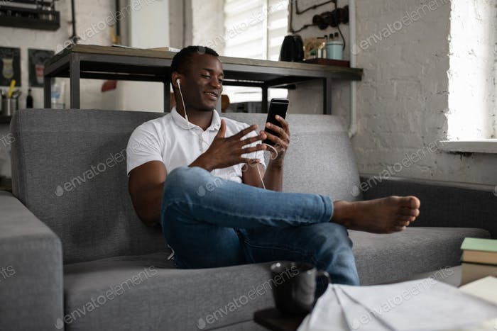 Relaxed black student having virtual meeting with classmates